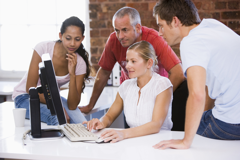 A picture of a girl keying in a computer and one woman and two men watching her work